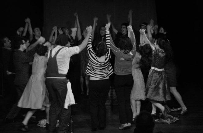 atores de teatro em círculo de mãos dadas levantadas